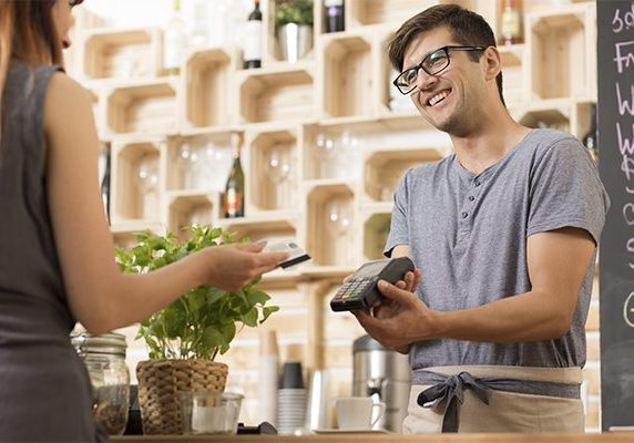 Shot of a smiling barista holding a payment terminal and a customer paying by card