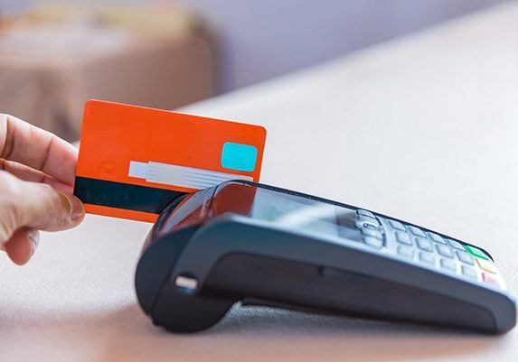 Hand Swiping Credit Card on POS terminal in Store.